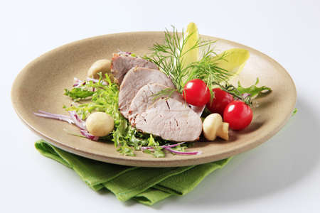 Roast pork tenderloin served with vegetables and mushrooms photo