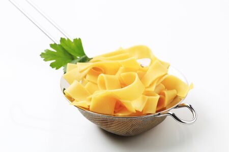 ribbon pasta: Cooked ribbon pasta in a metal sieve Stock Photo