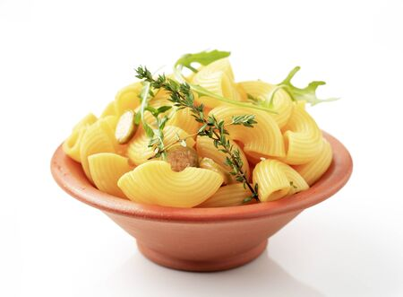 Bowl of macaroni with sliced capers and rocket photo