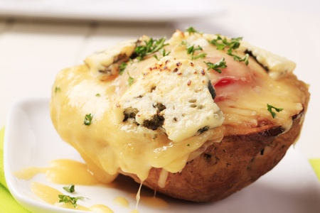melted cheese: Double cheese twice baked potato sprinkled with parsley Stock Photo