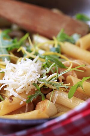 Pasta salad sprinkled with arugula and lemon zest and Parmesan Stock Photo - 9105182