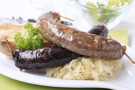 Blood sausage and white pudding with sauerkraut and baked potato photo