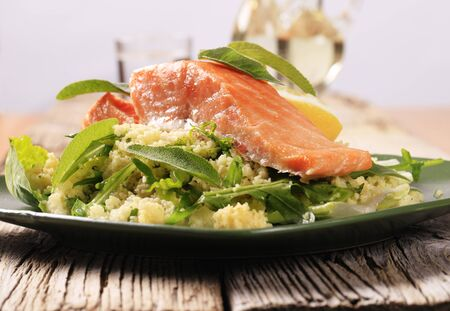 Roasted salmon fillet on a bed of couscous salad photo