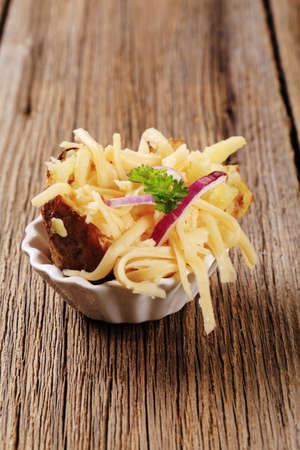 Baked potato sprinkled with grated cheese and onion Stock Photo - 9148655
