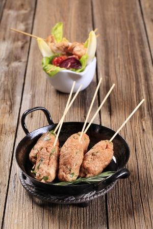 trivet: Raw minced meat kebabs on wooden skewers