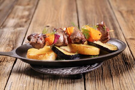 Beef or venison kebab with oranges served in a skillet  photo