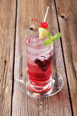 maraschino: Glass of iced drink garnished with lime and maraschino cherry