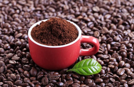 Freshly ground coffee in a red cup photo