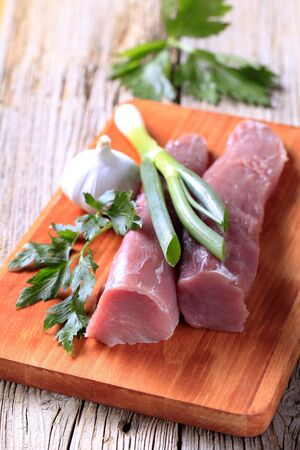Raw tenderloin of pork, spring onion and garlic photo