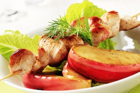 Roasted chicken skewer and slices of baked apple  photo