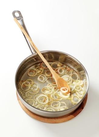 sautee: Frittura di anelli di cipolla in una padella - studio