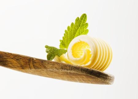 mantequilla: Detalle de un rizo de mantequilla en una cuchara de madera
