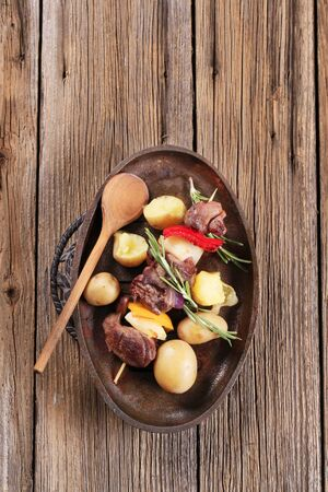 Venison shish kebab and new potatoes on a skillet photo