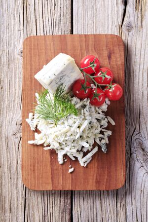 Blue cheese and fresh tomatoes on a cutting board photo
