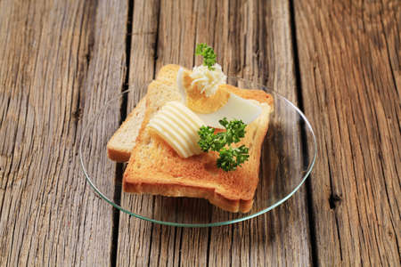 Two pieces of crispy toast, butter and boiled egg  photo