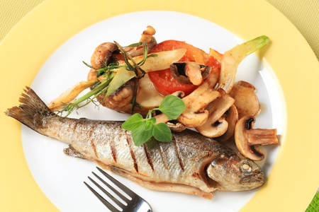 Pan fried trout with button mushrooms and tomatoes photo