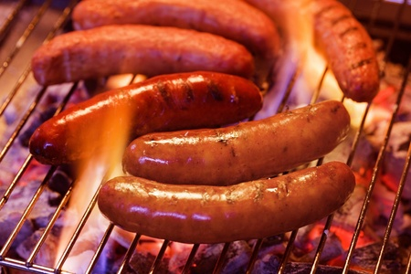 Grilling bratwursts on a charcoal grill photo