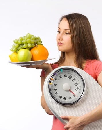 Young woman holding a weight scale and plate with fresh fruit  photo