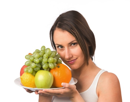 Young woman holding a plate with fresh fruit  photo