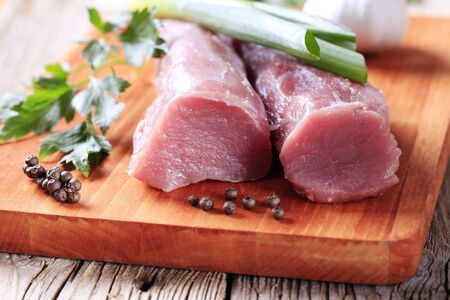 Raw tenderloin of pork on a cutting board photo
