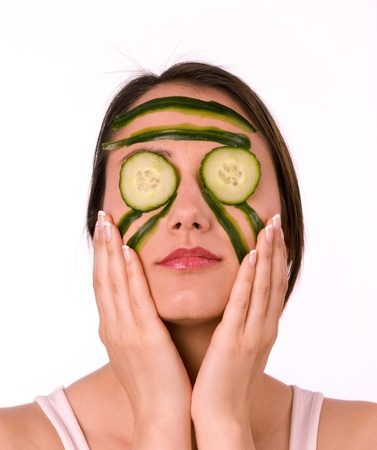 Young woman with her face covered with cucumber slices photo