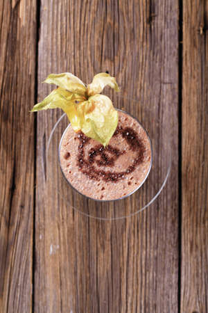 Glass of chocolate smoothie garnished with fresh fruit photo