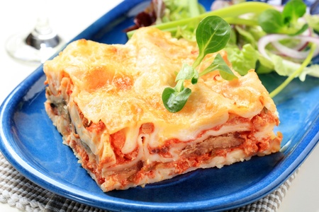 Portion of lasagna garnished with salad greens Stock Photo