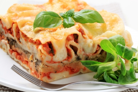 greens: Portion of lasagna garnished with salad greens Stock Photo