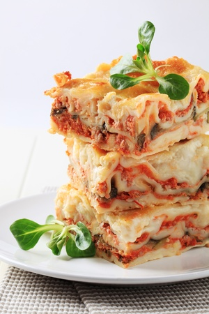 Stack of lasagne garnished with salad greens photo