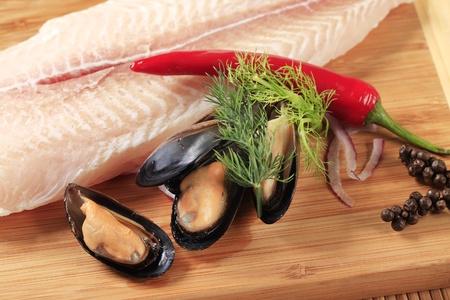 filete de pescado: Filete de pescado fresco y mejillones en un tablero de corte