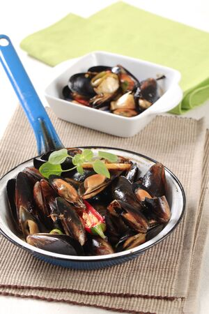 Steamed mussels in a frying pan photo