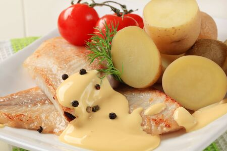 Pan fried fish fillets with potatoes and Hollandaise sauce photo