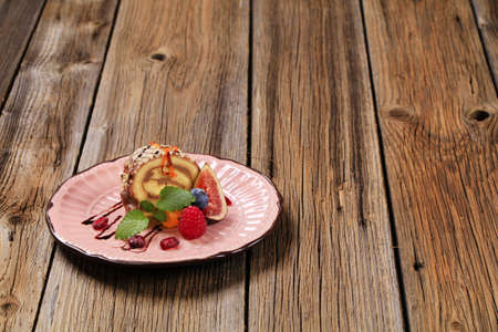 Chocolate Swiss roll garnished with fresh fruit photo