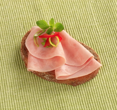 Thin slices of ham on brown bread photo