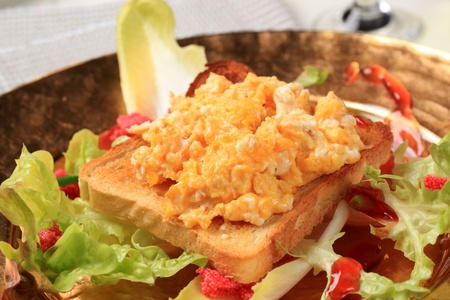 Toast and scrambled eggs on nest of fresh salad photo