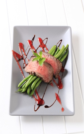 Slices of roast beef and string beans photo