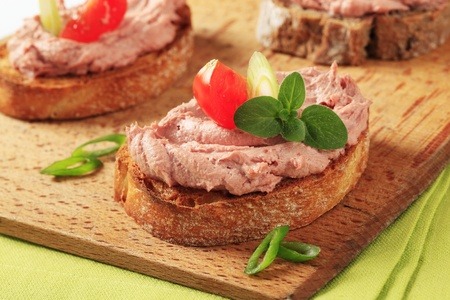 Slices of toasted bread with delicious liver pate photo