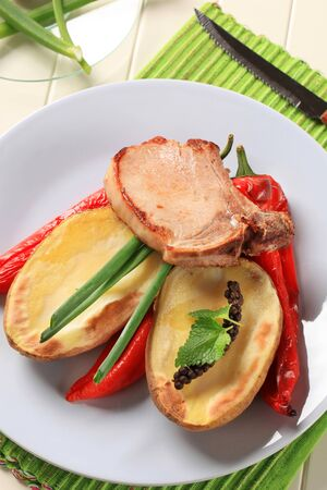 Pan fried pork chop with potato and red peppers photo