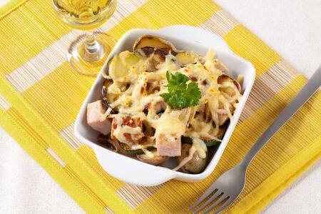 Pork and potato casserole topped with cheese photo