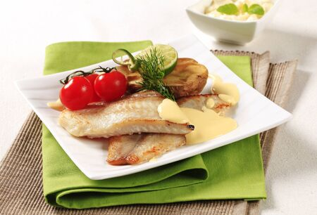 Pan fried fish fillets and Hollandaise sauce photo
