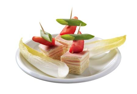 escarola: Canap�s de jam�n y queso y hojas de escarola Foto de archivo