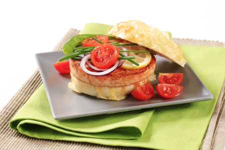 Pan fried salmon patty in cheese-topped bun  photo
