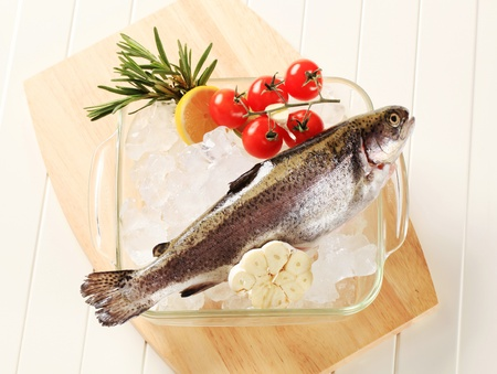 Fresh trout on ice in a glass dish photo