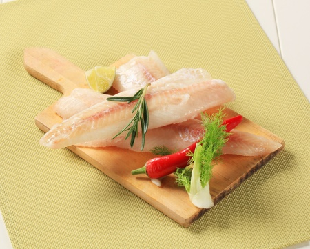 cod fish: Fresh fish fillets on a cutting board