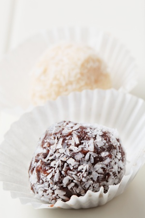 chocolate balls: Coconut-coated chocolate balls in paper cases Stock Photo