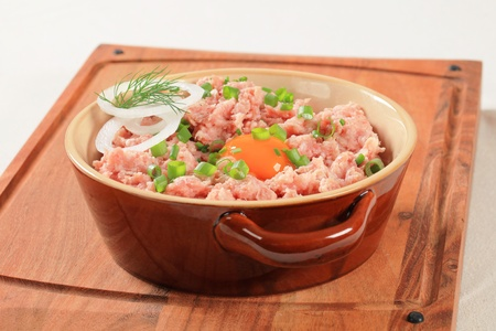 Ground meat and other ingredients in a ceramic pot photo