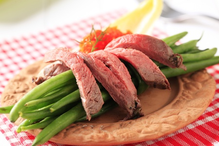 Strips of roast beef and string beans photo