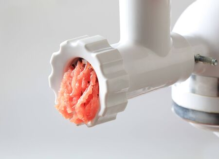 Fresh minced meat coming out of a meat grinder photo