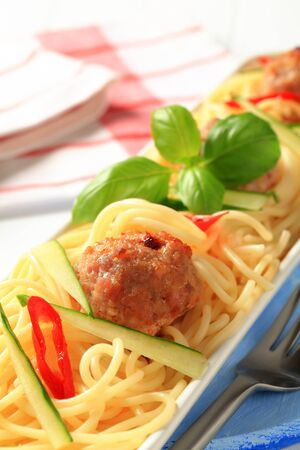 Meatballs on a bed of cooked spaghetti photo