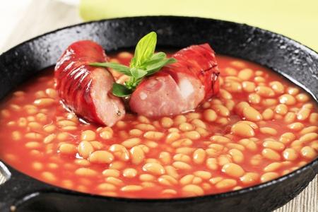 Fèves au lard et des saucisses dans une poêle à frire
